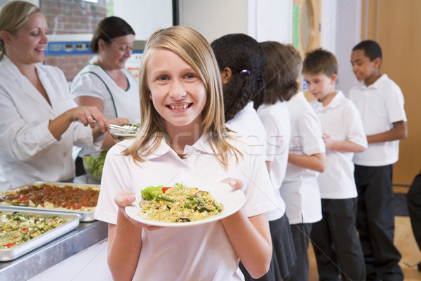Schoolgirl holding plate of lunch in school cafeteria Stock photo © monkey_business