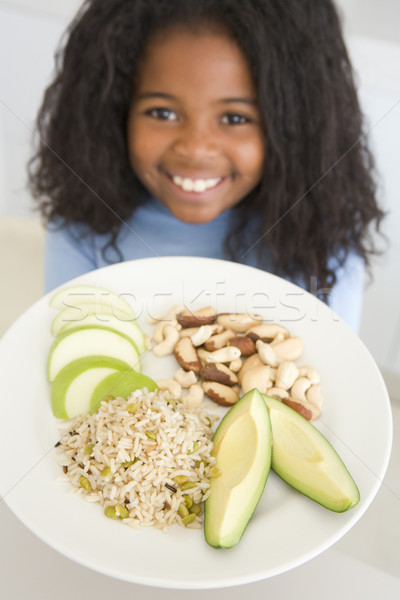 Young girl in kitchen eating rice fruit and nuts smiling Stock photo © monkey_business