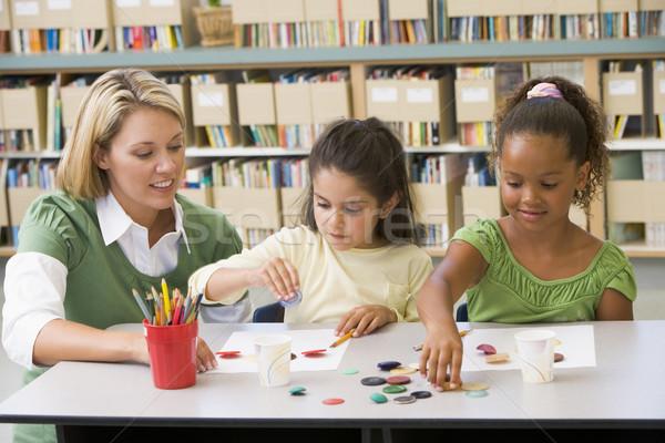 Kindergarten teacher sitting with students in art class Stock photo © monkey_business