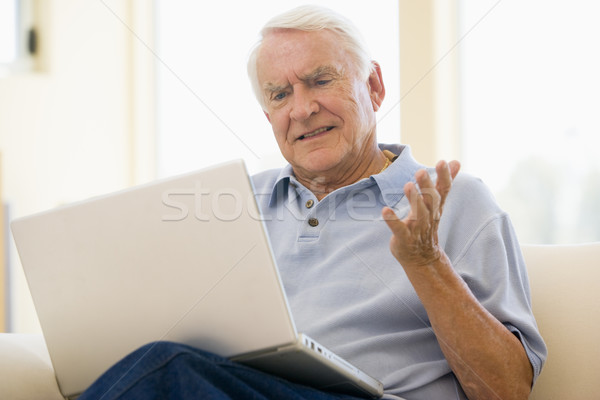 Man in living room with laptop Stock photo © monkey_business