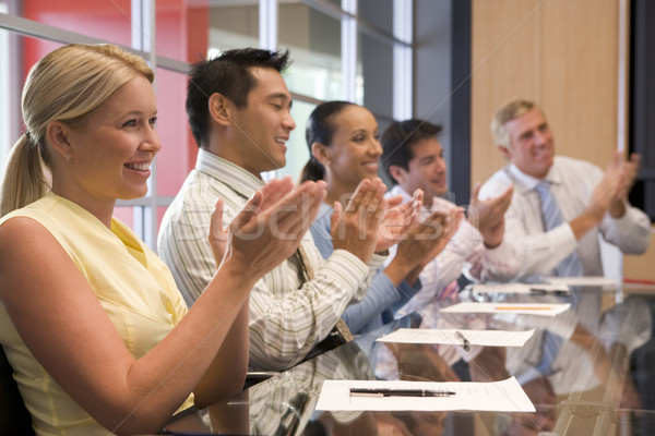 Five businesspeople at boardroom table applauding and smiling Stock photo © monkey_business