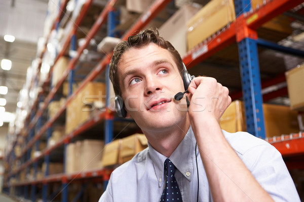 Businessman Using Headset In Distribution Warehouse Stock photo © monkey_business