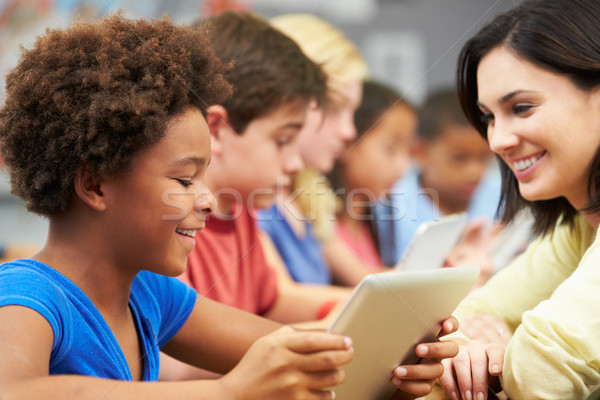 Pupils In Class Using Digital Tablet With Teacher Stock photo © monkey_business