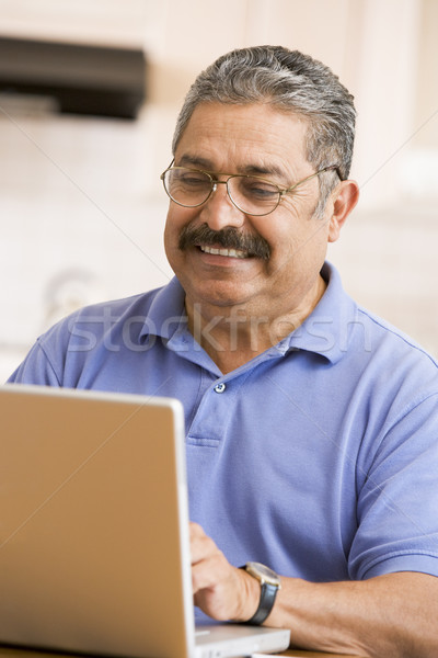 Man in kitchen with laptop smiling Stock photo © monkey_business