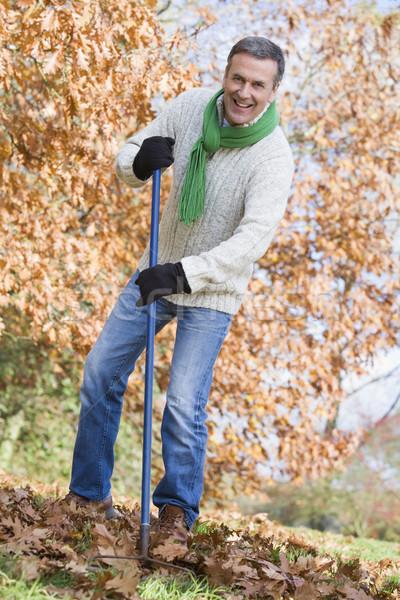 Senior man tidying autumn leaves Stock photo © monkey_business