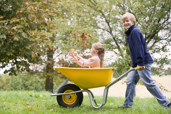 Young boy pushing girl in wheelbarrow Stock photo © monkey_business