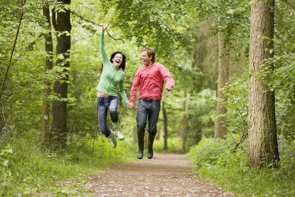 Couple jumping on path holding hands and smiling Stock photo © monkey_business