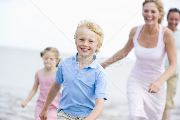 Family running on beach smiling Stock photo © monkey_business