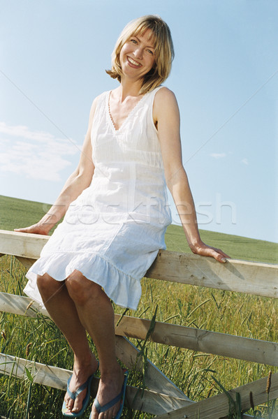 Woman sitting on fence outdoors smiling Stock photo © monkey_business