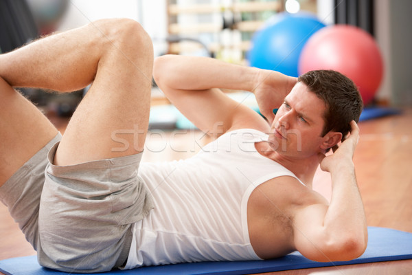 Man Doing Stretching Exercises In Gym Stock photo © monkey_business