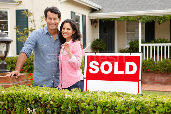 Hispanic couple outside home with sold sign Stock photo © monkey_business