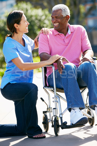 Cuidador empujando altos hombre silla de ruedas mujer Foto stock © monkey_business
