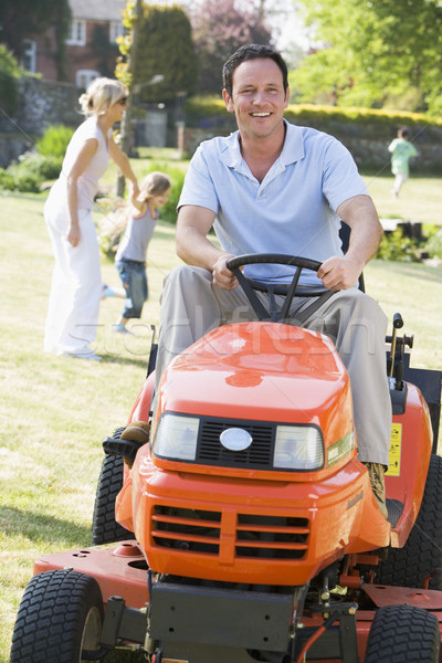 Man outdoors driving lawnmower smiling with family in background Stock photo © monkey_business