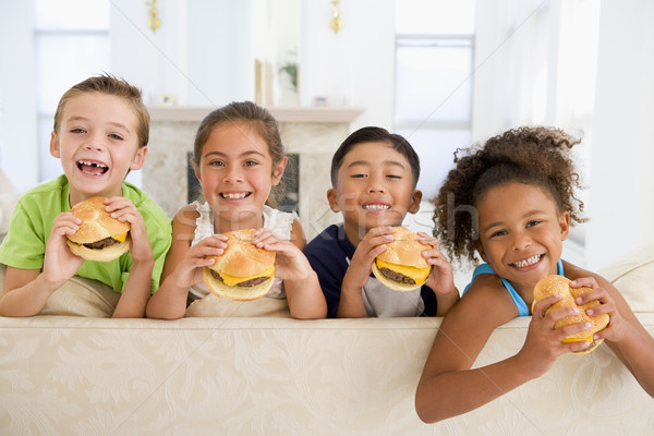 Four young children eating cheeseburgers in living room smiling Stock photo © monkey_business