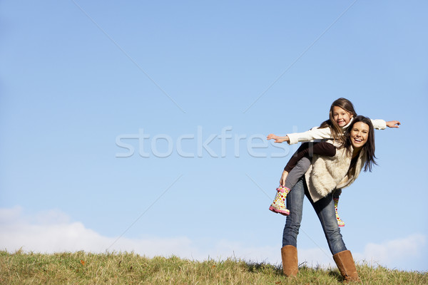 Mother Giving Her Daughter A Piggy Back Ride Stock photo © monkey_business
