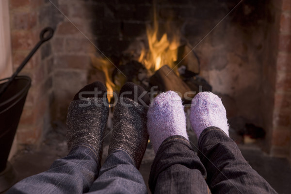 Stock photo: Couple's feet warming at a fireplace
