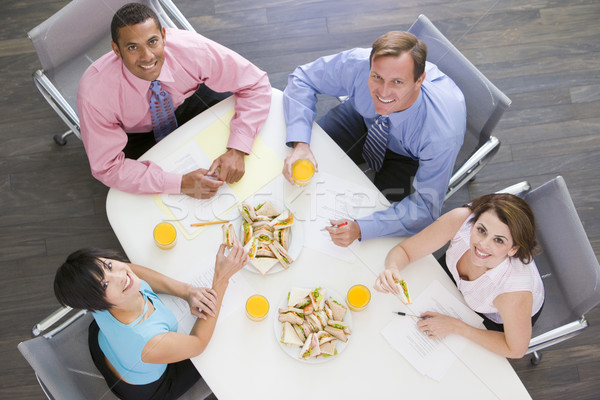Four businesspeople at boardroom table with sandwiches smiling Stock photo © monkey_business