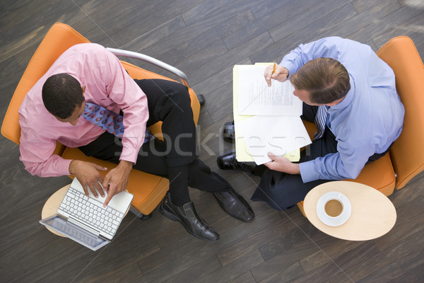 Two businessmen sitting indoors with coffee laptop and folder Stock photo © monkey_business