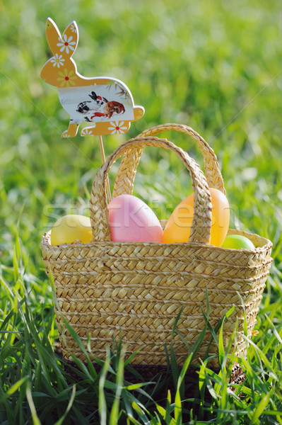 Coloured Easter eggs in a basket padded out with rabbit decorations Stock photo © Moravska