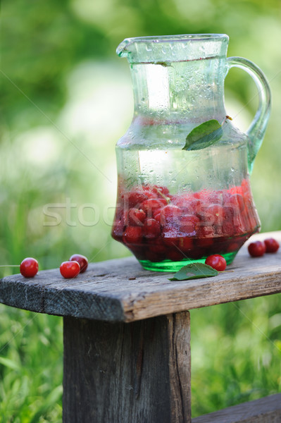 Jarro frio água doce cerejas mesa de madeira jardim Foto stock © Moravska