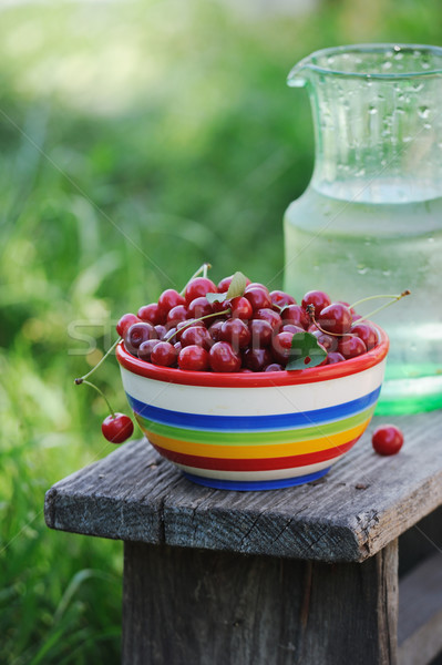 Jug of cold fresh water with cherries on wooden table in the garden Stock photo © Moravska