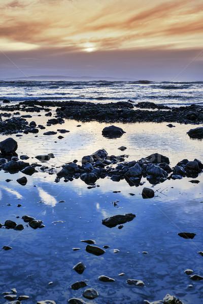 calm yellow sunset over rocky beach Stock photo © morrbyte