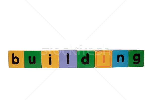 building in wood play block letters against white Stock photo © morrbyte