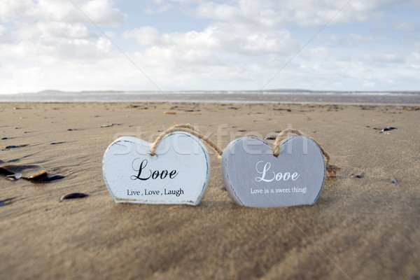 couple of inscribed wooden love hearts in the sand Stock photo © morrbyte