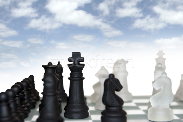 Stock photo: chess pieces isolated against cloudy sky