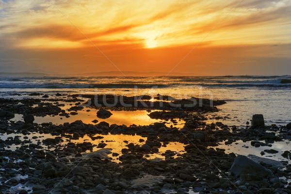deep orange reflections at rocky beal beach Stock photo © morrbyte