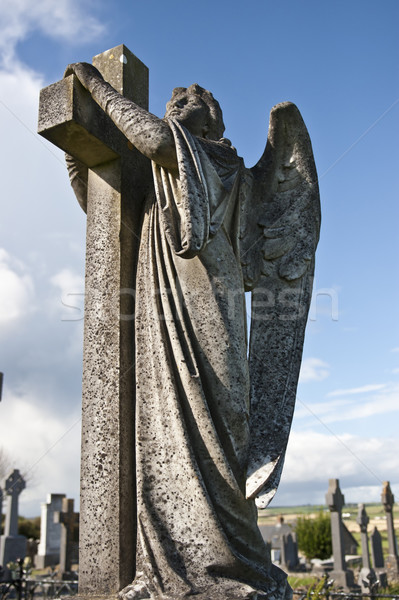 Stock photo: Angel statue embracing a cross and celtic graveyard