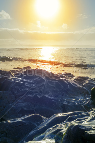 waves over hot sunset rocks Stock photo © morrbyte