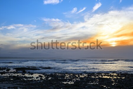 beautiful yellow sunset sky over rocky beach Stock photo © morrbyte