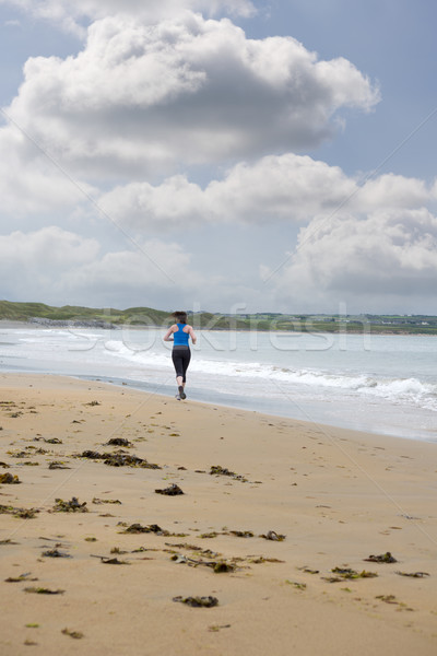 young woman jogging on the beach Stock photo © morrbyte