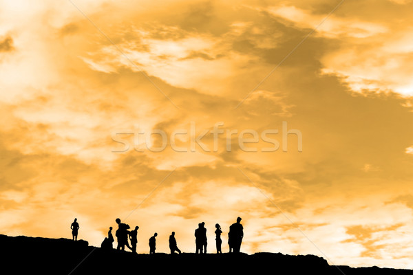 silhouette of people on peak of the cliff edge Stock photo © morrbyte