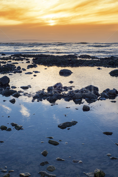 beautiful mellow sunset over rocky beach Stock photo © morrbyte