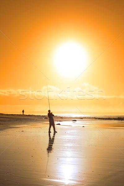 lone fisherman fishing on the sunset beach Stock photo © morrbyte