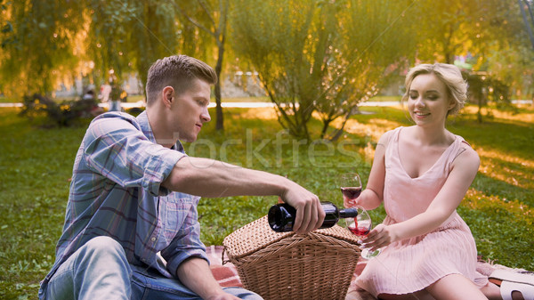 Man filling glasses with ruby wine and saying toast to beloved, anniversary Stock photo © motortion