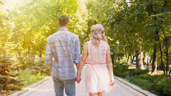 Beautiful young couple strolling through sunlit bright green park, romantic date Stock photo © motortion