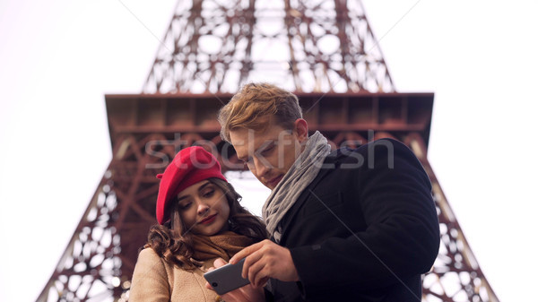 Male and female tourists searching destination in Paris on map in mobile app Stock photo © motortion