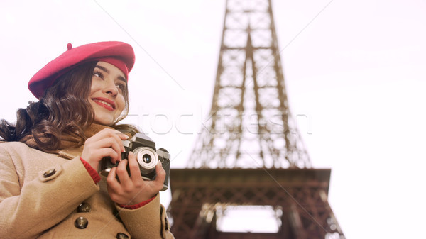 Creative girl holding camera in hands, enjoying photography hobby in Paris Stock photo © motortion