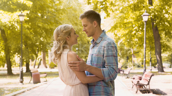 Loving couple gently embracing, enjoying long-awaited date in park, first love Stock photo © motortion