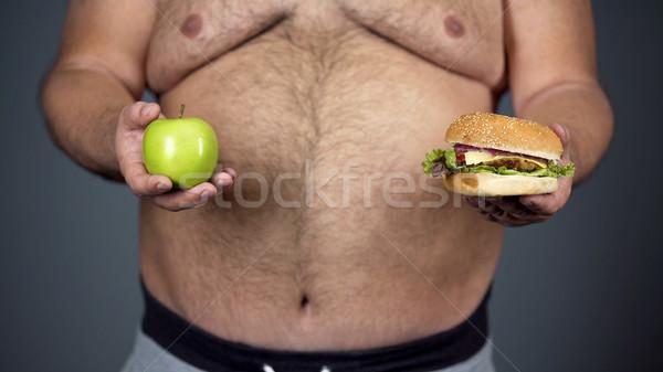 Kövér férfi választ alma hamburger egészséges étrend közelkép Stock fotó © motortion