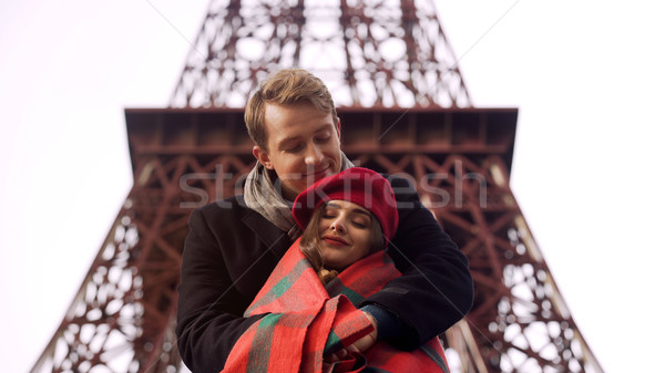 Attentive man wrapping his frozen beloved lady in blanket, openair date in Paris Stock photo © motortion