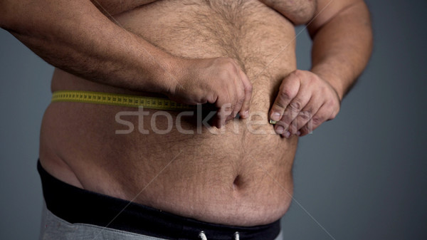 Sad overweight man unable to measure his waist, fat tummy with stretch marks Stock photo © motortion