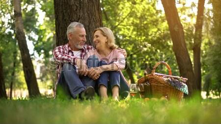 Handsome boyfriend telling interesting stories to girlfriend during picnic Stock photo © motortion