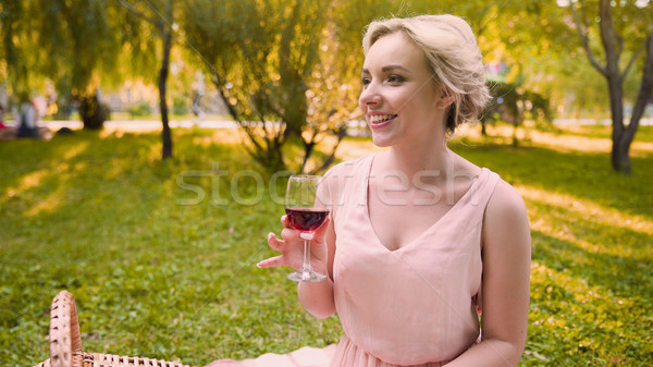 Pretty girl sipping wine in shade of park trees spending wonderful time in park Stock photo © motortion