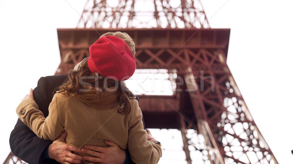Enamored man passionately kissing beloved woman on romantic date in Paris Stock photo © motortion