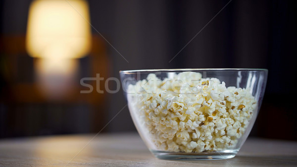 Big glass bowl of salty popcorn standing on table, treatment for home party Stock photo © motortion