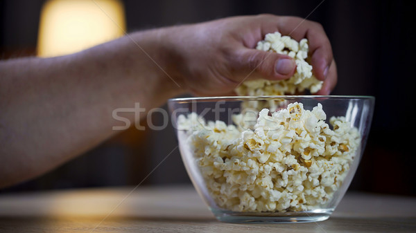 Closeup of male hand taking popcorn from bowl on table, unhealthy food addict Stock photo © motortion